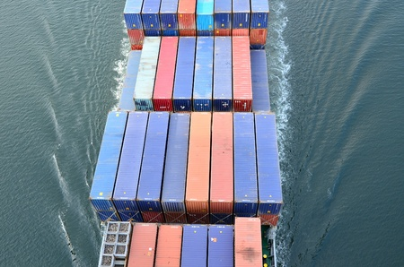 VARNA, BULGARIA - JANUARY 20: Cargo ship DS BLUE OCEAN (Flag: United Kingdom, IMO: 9341976) sails into open sea on January 20, 2011 in Varna, Bulgaria. Ship`s next destination is Island of Malta. Containers on board the ship seen from above.
