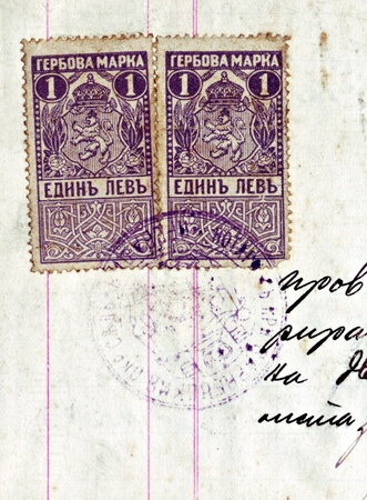 levy: BULGARIA - CIRCA 1920: Fiscal stamp printed in Bulgaria, coat of arms of Bulgaria, is used to collect taxes and duties, circa 1920. Some handwriting and a seal are also visible.