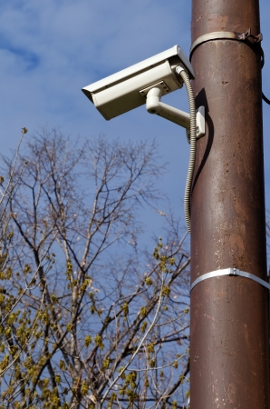 prying: Surveillance camera mounted on a post looking down  Stock Photo