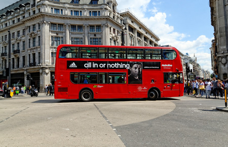 route master: LONDON - JULY 1, 2014: A London red bus bearing Adidas advertisement crossing at Oxford Circus in London. Editorial