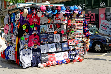 souvenirs: LONDON - JULY 1, 2014: Street vendor offers various colorful souvenirs at Oxford Street, where he competes with large supermarket chains.