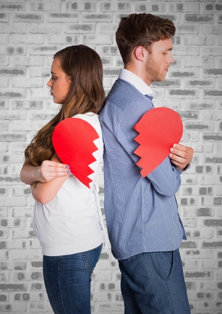 Depressed couple standing back to back holding broken heart Stock Photo