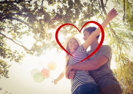 Composite image of romantic couple embracing in park with a drawn red heart shape