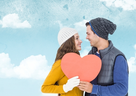 Composite image of romantic couple holding heart shape against sky Stock Photo