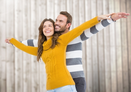 Happy couple pretending to fly against wooden background Stock Photo