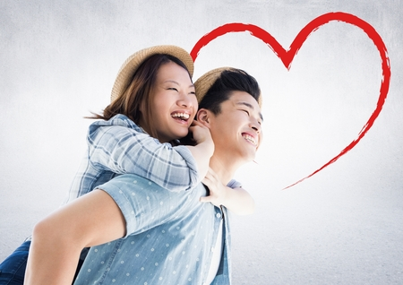 Happy man giving woman piggyback against white background with red heart shape