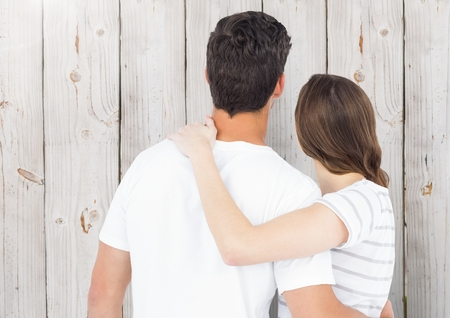 Rear view of couple embracing against wooden background Stock Photo