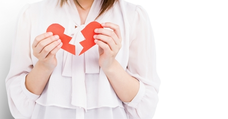 Mid section of woman holding broken heart Stock Photo