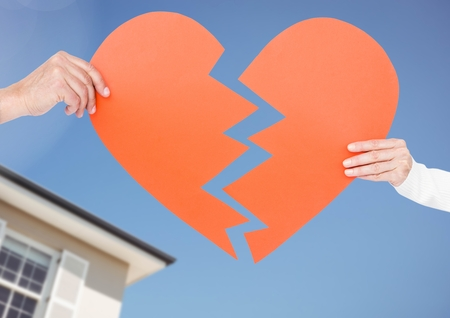 Composite image of couple holding a broken heart against sky