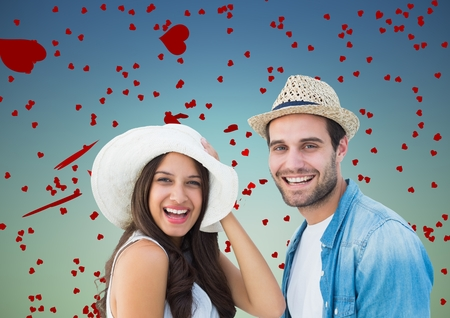 Romantic couple having fun against blue background with hearts Stock Photo