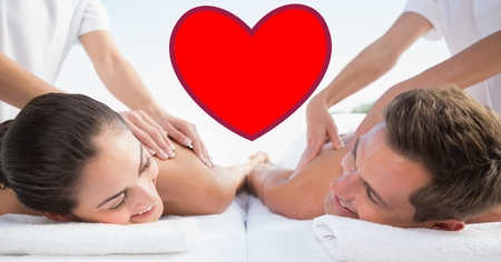 Composite image of masseur giving massage to couple at spa Stock Photo