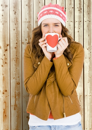 Portrait of woman holding a mug with a heart shape on it in front of wooden background