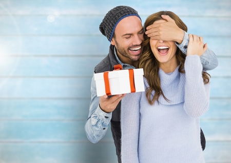 Happy man holding a gift box and covering eyes of woman against wooden background