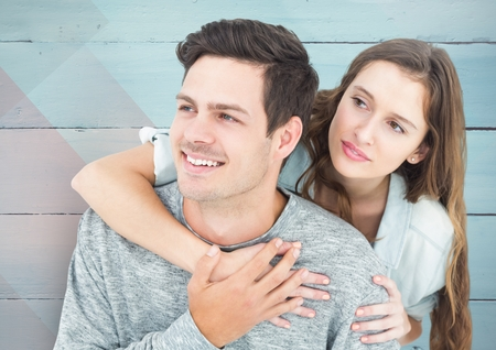 each: Happy couple embracing each other in front of wooden background