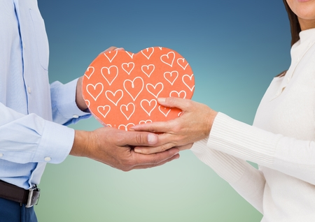 outdoor blank billboard: Mid section of couple holding heart shape box against blue background