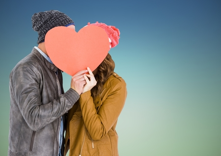 Romantic couple hiding their face behind heart against blue background