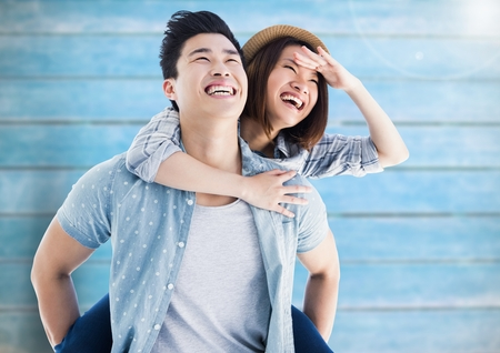 Composite images of happy man giving woman piggyback against wooden background Stock Photo