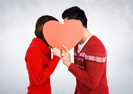 Romantic couple hiding their face behind heart against white background Stock Photo