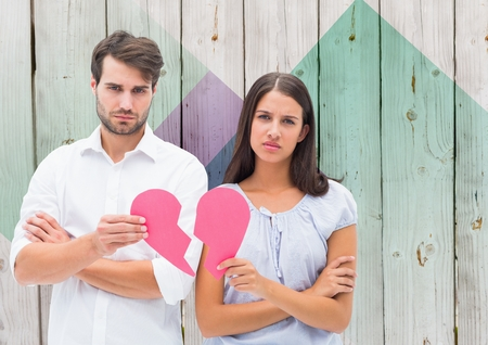 Portrait of depressed couple holding broken heart against wooden background Stock Photo