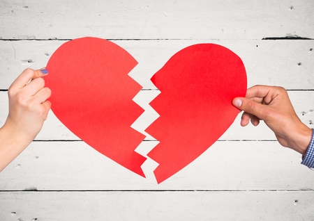 Hands of couple holding a broken heart against wooden background Stock Photo