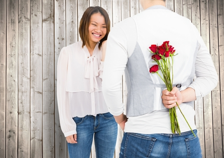 red rose black background: Smiling couple with man hiding roses in his back against wooden background