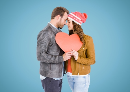 Romantic couple holding a heart against blue background