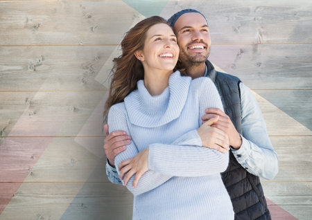 thirties: Happy couple embracing against wooden background Stock Photo