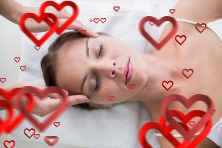 Composite image of red hearts and masseur giving massage to woman at spa