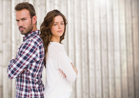 Unhappy couple standing back to back against wooden background Stock Photo