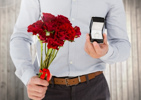 midsection: Mid-section of man holding engagement ring and flower bouquet against wooden background