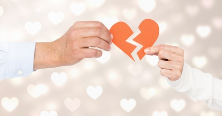 Hands of couple holding a broken heart against bokeh Stock Photo