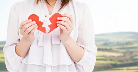Mid-section of a woman holding a broken heart on a sunny day Stock Photo