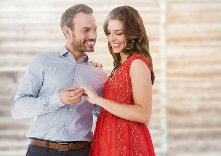 Composite image of happy engaged couple looking at engagement ring