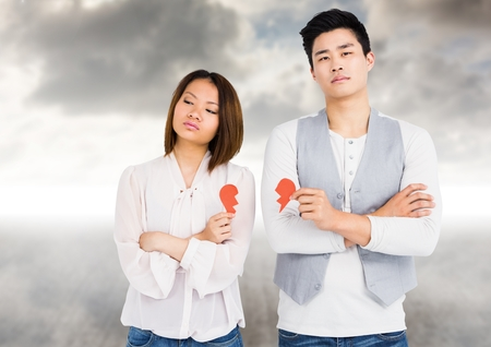 Composite images of depressed couple holding broken heart against storm clouds