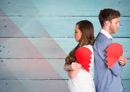 Sad couple holding broken heart against wooden background