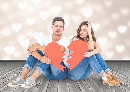 Composite image of sad couple holding broken heart