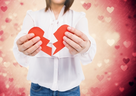 Mid-section of woman holding a broken heart against digitally generated background