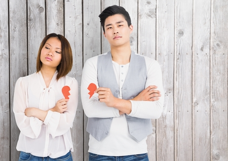 sad heart: Sad couple holding broken heart against wooden background