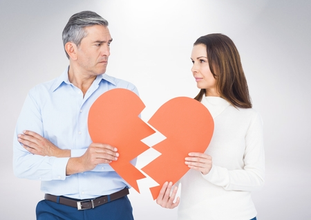 Mature couple holding a broken heart against white background Stock Photo