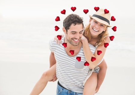 Composite image of elderly couple at beach with red valentines hearts Stock Photo