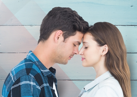 Romantic couple standing with closed eyes against wooden background