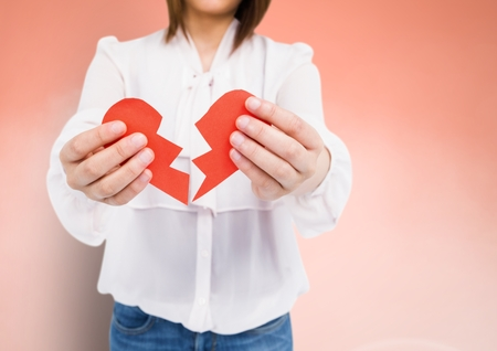 Mid-section of a woman holding a broken heart against peach background