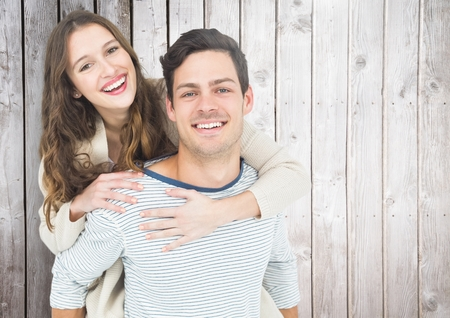 Man giving piggy back to beautiful woman against wooden background