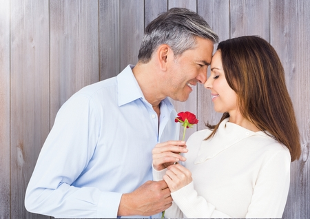 man holding transparent: Mature man giving red rose to woman against wooden background
