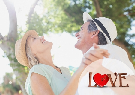 land locked: Composite image of love text and senior couple dancing on a sunny day