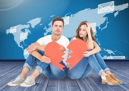 Composite image of couple holding a broken heart against world map background Stock Photo