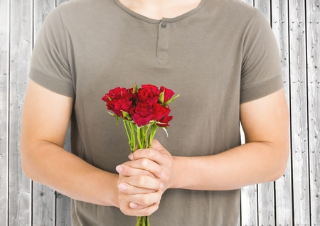 midsection: Mid-section man holding bunch of red roses against wooden background