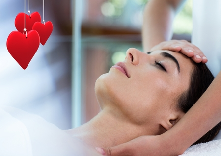 Composite image of red hanging hearts and beautiful woman receiving a head massage Stock Photo