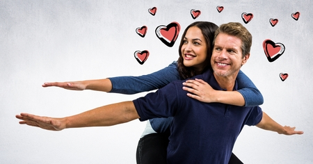 Composite image of Couple piggy back against white background with hearts valentine Reklamní fotografie