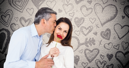 strife: Mature man kissing while giving a red rose to woman against hearts background